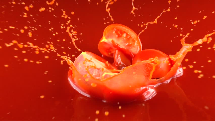 Red tomato falling into tomato juice and splitting into four quarters. Slow motion video