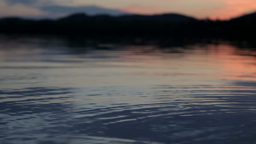 shallow focus on the foreground of calm lake water at dusk on Lows lake, Adirondack state park,New York, USA.