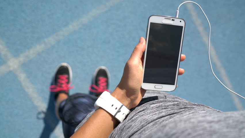 Runner girl holding smartphone using touchscreen for choosing music or texting sms on app before running on track. Female athlete woman feet and leg closeup with smartwatch and hand touching display.