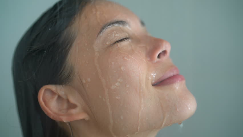 Spa woman showering relaxing under running water in hot shower. Closeup of Asian female adult face enjoying relaxation time meditating in warm bath cleaning face and body.