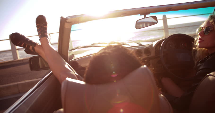 Two young women enjoying a summer sunset on seaside sitting in a vintage convertible with sunflare | Shutterstock HD Video #15173233