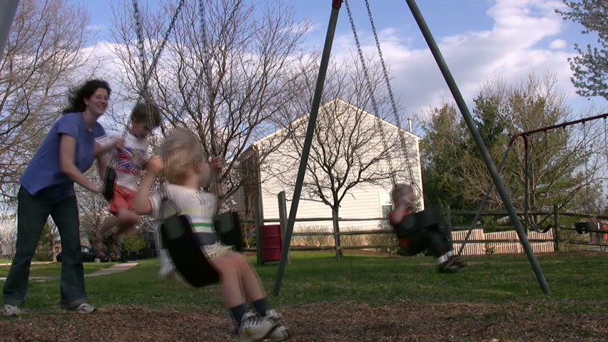 children enjoy a beautiful spring day swinging at the playground