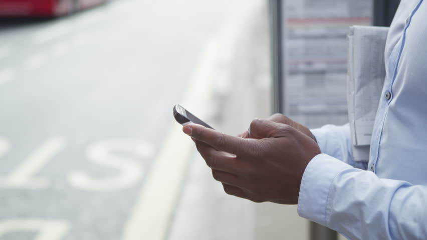 4K Attractive man looking at mobile phone while waiting at London city bus stop | Shutterstock HD Video #15195328
