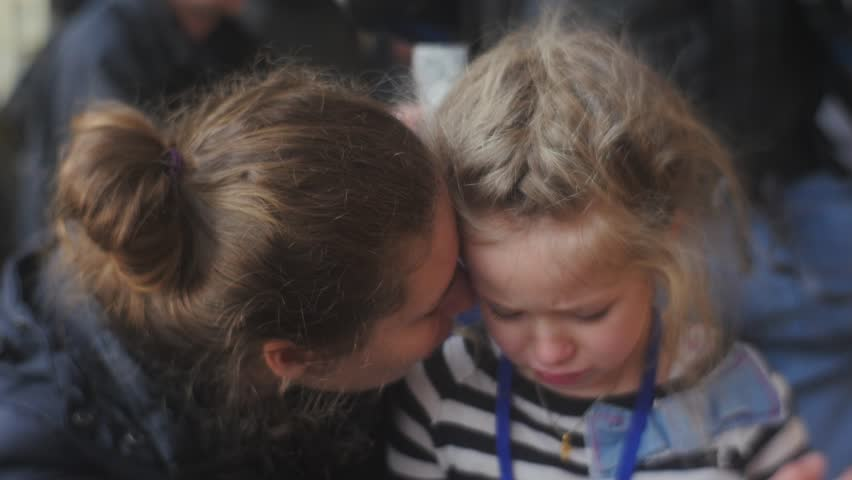 Woman Gives a Hug to Her Daughter and Smiling, Little Blonde Girl is Crying, Snuggling to Mom, Talking Something, Looking Somewhere, Tears Are Coming Down, Wet Face, Then Child Stops Crying