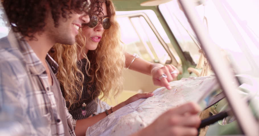 Hipster mixed race man and hipster caucasian woman holding open a map and looking at it in the front seat of a retro van
