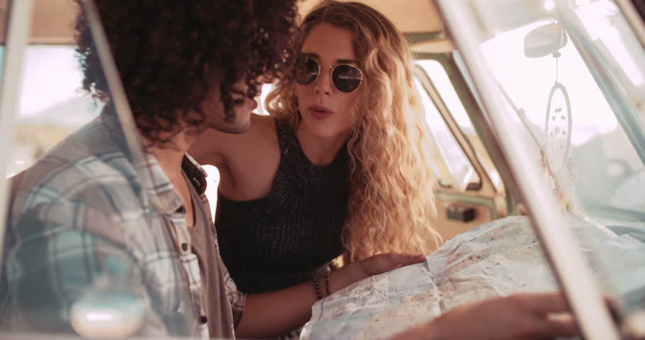 Hipster mixed race man and boho caucasian woman holding open a map and looking at it in the front seat of a retro van, the couple ready for their road trip to the beach