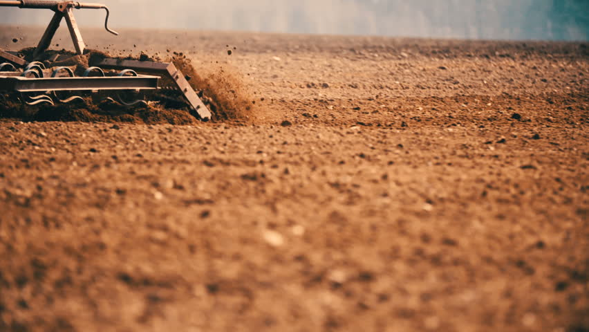 Tractor cultivating land in extreme close up slow motion.
