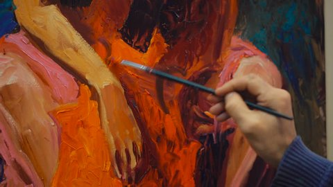 Somebody is painting some picture with paintbrush. Woman on canvas