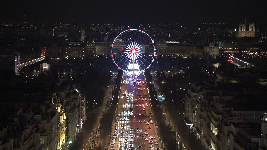 Aerial night view of the famous ferris wheel in Paris as seen from the top of the Arc de Triomphe along the Champs Elysees boulevard. The Notre Dame cathedral can be seen on the right of the frame. | Shutterstock HD Video #15323878