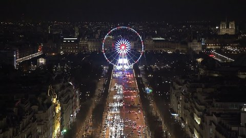 Aerial night view of the famous ferris wheel in Paris as seen from the top of the Arc de Triomphe along the Champs Elysees boulevard. The Notre Dame cathedral can be seen on the right of the frame.