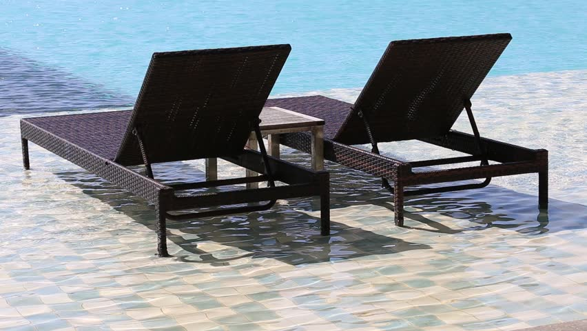 two deck chairs in the swimming pool at a tropical resort hd stock video clip - Swimming Pool Deck Chairs