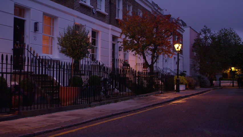 4K Night time view of a row of terraced town houses in a wealthy London suburb. UK -- January, 2015