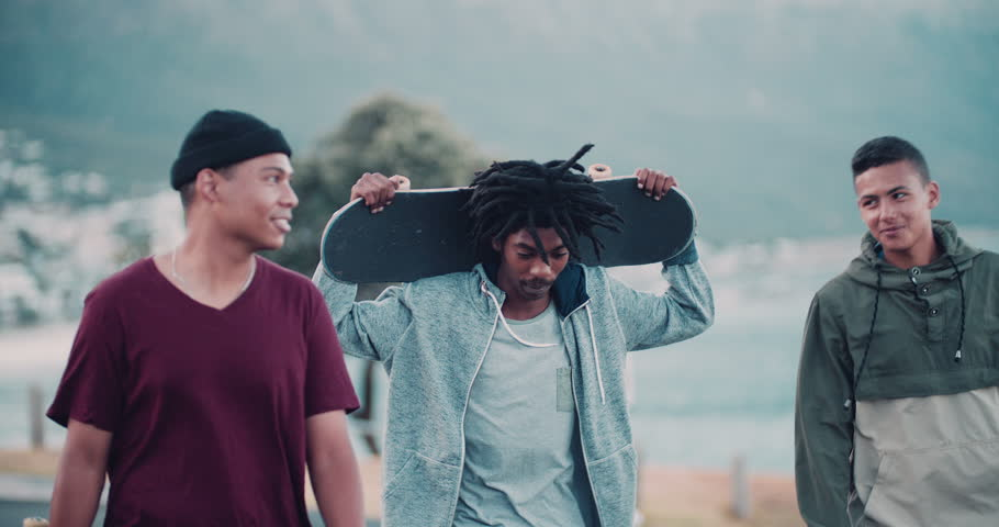 Multi-Ethnic group of skater friends hanging out, holding skateboards and smiling with one holding skateboard behind head with both hands at seaside