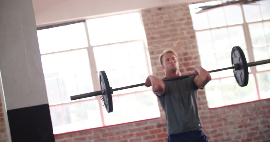 Young adult athletic man doing weight training exercise during a crossfit  workout at the gym