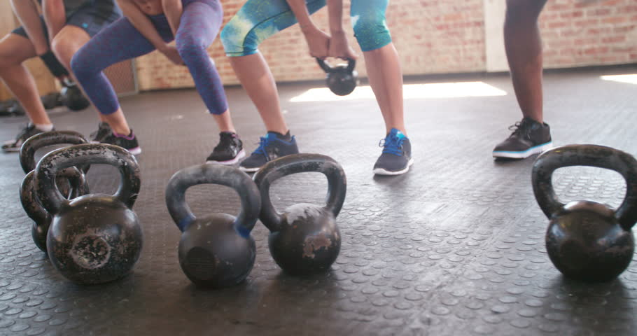 Focus On Kettlebells Crossfit Training Group Of Young Athletes Doing Kettlebell Exercise During A Workout At The Gym Stock Footage