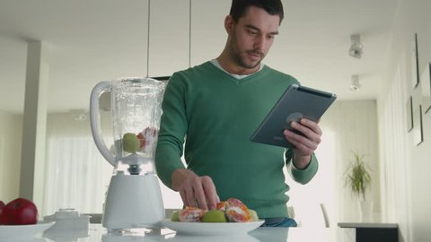Handsome man is preparing a smoothie while using a tablet computer in the kitchen. Shot on RED Cinema Camera in 4K (UHD).