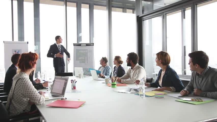 Handsome young director giving presentation to colleagues in conference room | Shutterstock HD Video #15414658