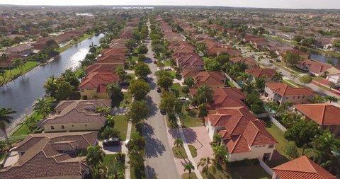 Aerial over a treelined neighborhood in ANYWHERE USA suburbs.