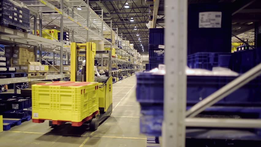 Man driving forklift and loading cargo on rack in warehouse