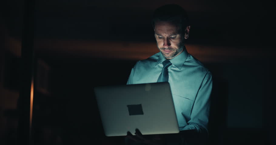 Side view of a mature business man in blue shirt and blue tie working in dark office late at night