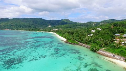 Aerial view (landscape) of tropical paradise beach (coast) with white sand and azure sea water of Indian Ocean, summer sunny day, Anse Royale, Mahe Island, Seychelles Islands vacation, 4k UHD ProRes