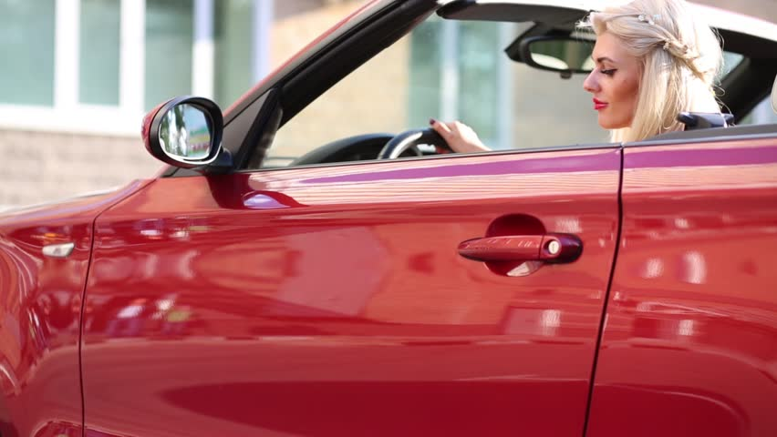 Blonde Young Woman Sits In Red Sport Car And Opens Door At Summer Day   HD