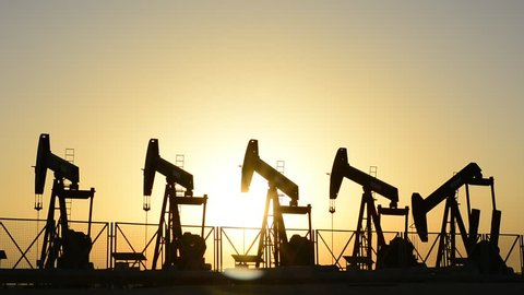 Silhouette of crude oil pumps at sunset