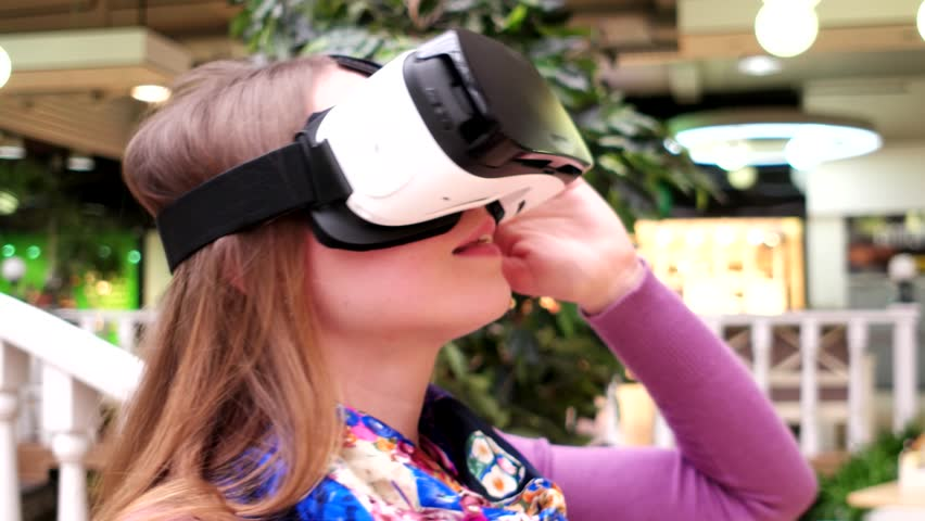 Kherson, Ukraine - 23 MAR 2016: Smiling girl looks through glasses online presentation with virtual reality technology in Kherson, Ukraine 23 MAR 2016