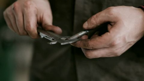 a Man Who is Master and Wearing a Brown Shirt Holding Screw and Calipers. he Measures the Length and Width of the Screw and the Length and Width of the Screw Head. Screw and Calipers Made From Metal