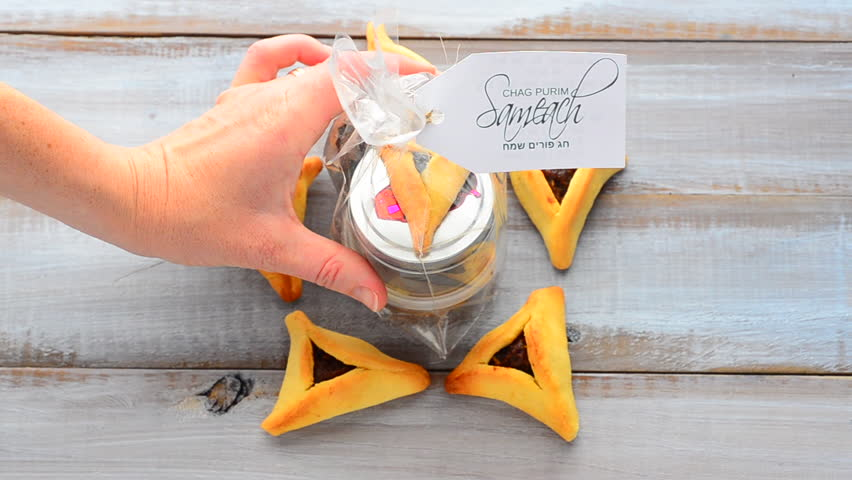 Woman hand placing a Purim basket (Mishloach manot) in side a Star of David made out of Purim Cookies - Hamentashen (Ozen Haman) for Purim Jewish Holiday. Copy space