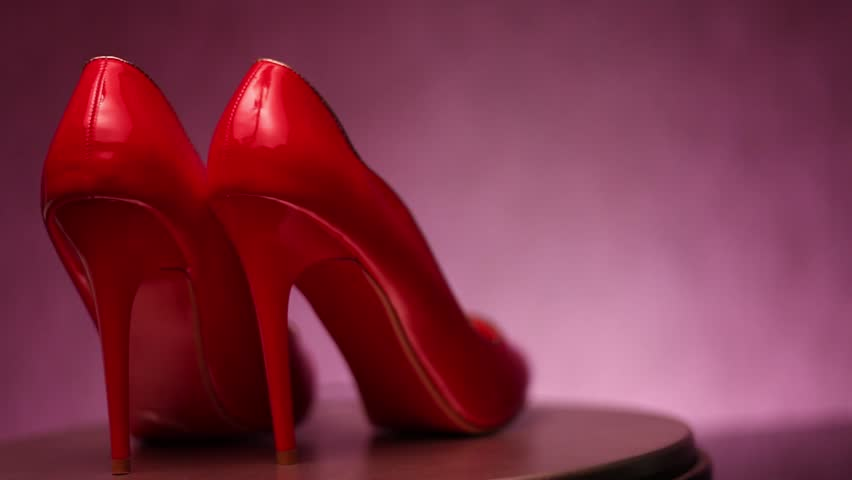 Red, glossy stiletto high heel shoes on shop display spinning