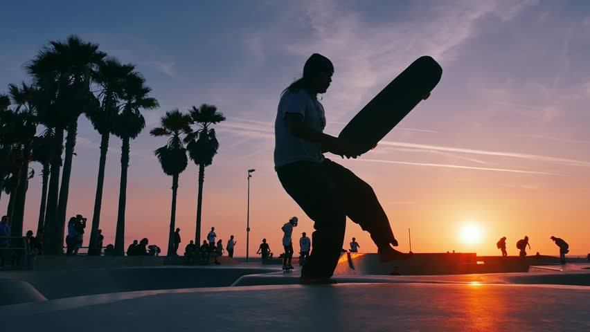Skateboarder silhouettes skateboarding in Venice Beach skate park at sunset. Slow motion.