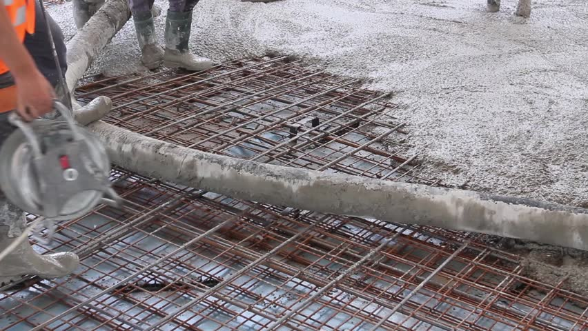 Workers are spreading concrete over big reinforced floor for Poured concrete foundation