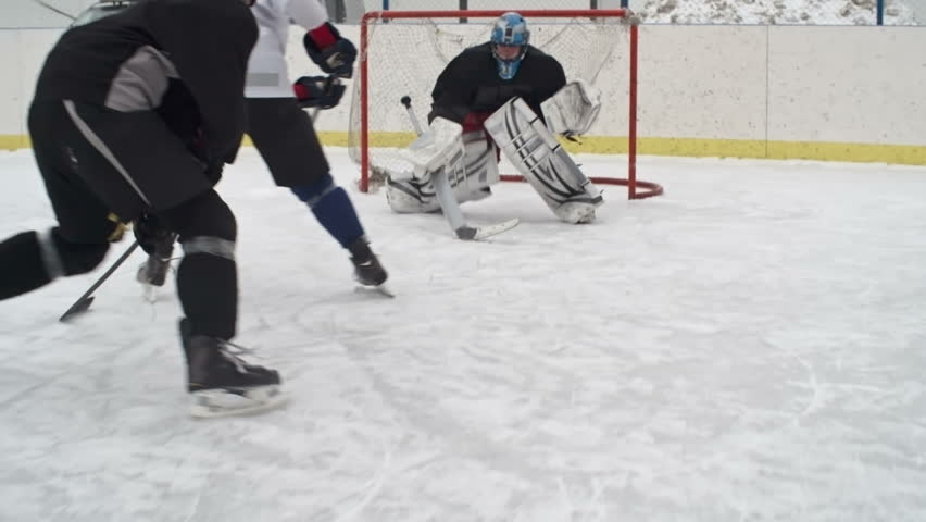 Hockey forward carrying a puck, skating past an opposing defenseman and taking a slap shot; goaltender preventing the scoring of a goal by catching the puck