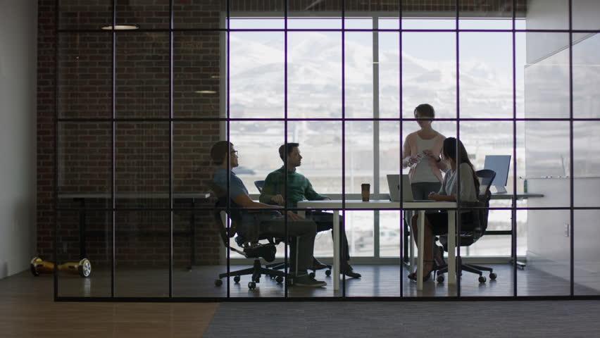 Wide panning shot of business people talking in meeting / Lehi, Utah, United States