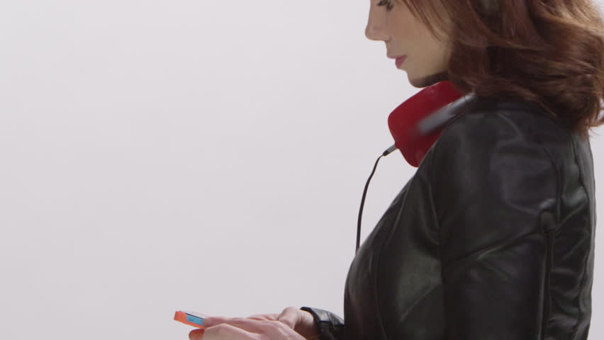 Beautiful model wearing headphones listening to digital music from a streaming service on her smart phone | Shutterstock HD Video #15521188