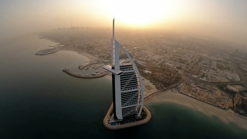 Fly over Jumeirah Beach near Burj Al Arab hotel in Dubai, UAE. Burj Al Arab is a luxury 5 star hotel built on an artificial island in front of Jumeirah beach. Helicopter aerial view at sunrise