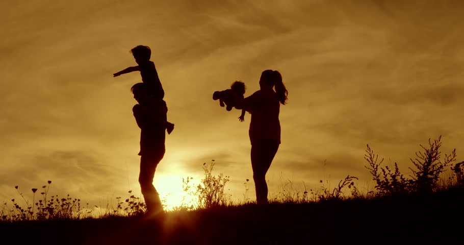 Happy family fun and hugs silhouetted dawn with orange sky