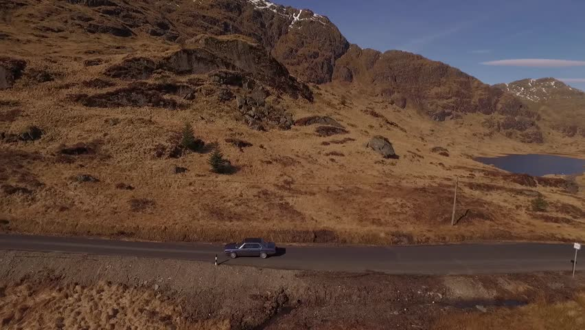Aerial pan of 1985 BMW 525e driving on a mountain road in the Scottish highlands on a sunny day
