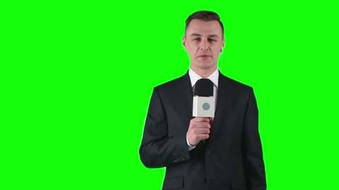 TV journalist standing on green screen background with microphone and talking