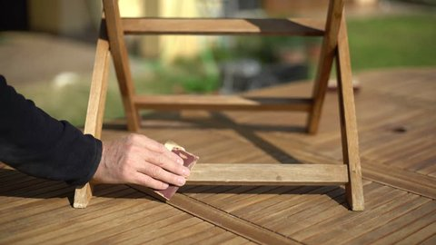 Closeup of restoring a wooden chair with sandpaper. Garden furniture.