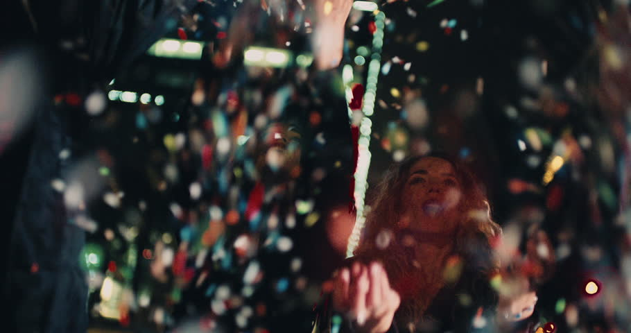 Teenager hipster friends celebrating a night party by blowing colourfull confetti with city lights in the background | Shutterstock HD Video #15559333