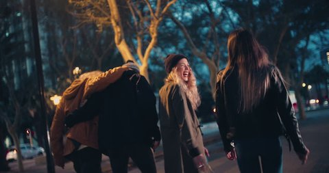 Young happy couples in winter outfits embracing while taking a night walk outside in the city