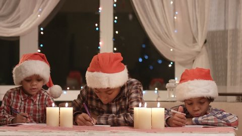 Little Santas writes a letter. Christmas kids writing letter. Congratulating pen-friends on Christmas. Best wishes for a friend.