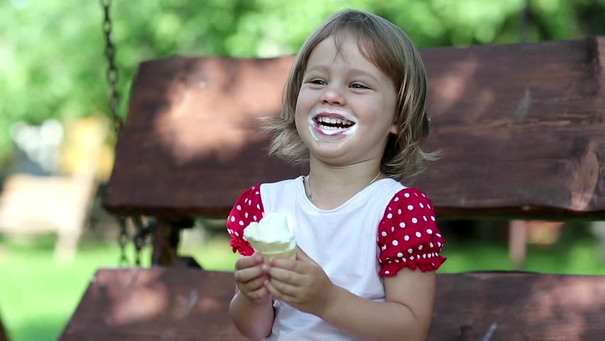 Little girl sits on the swing bench eats ice cream smiles and laughs. Very funny girl