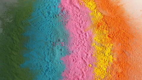 Colorful rainbow holi powder bounces off white canvas background in shockwave pattern of green blue pink and orange, slow motion, closeup