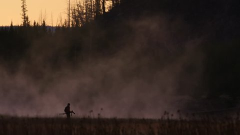 Wildlife nature photographer in Yellowstone National Park walking with tripod in early morning near a steamy river. USA. 4K.