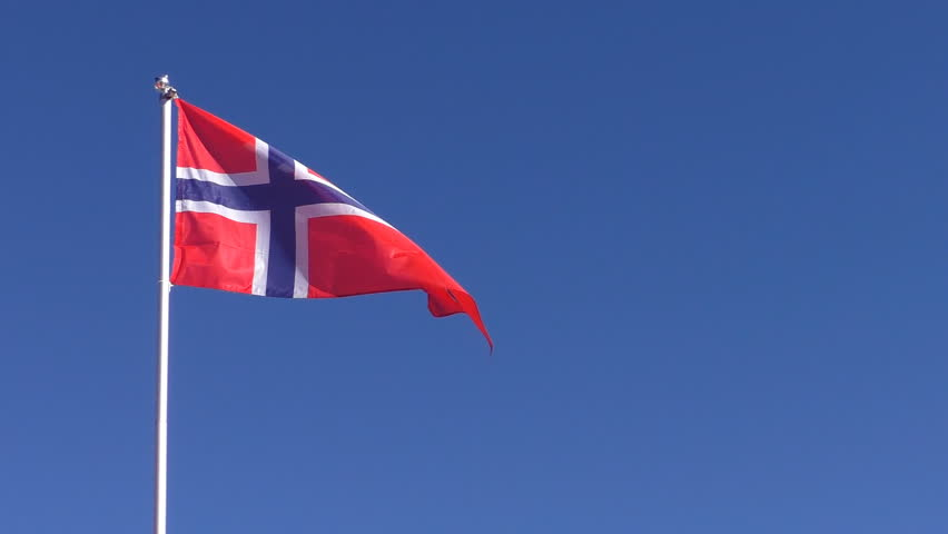 Red with blue cross Norwegian national flag is slowly waving in the blue clear sky on white flagpole