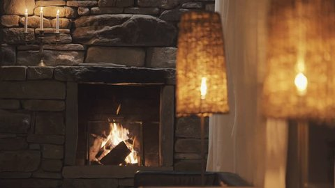 Calm fireplace with warm light at night with candle and wine