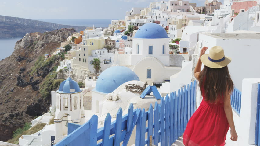 Tourist travel woman in Oia, Santorini, Greece. Happy young woman walking on stairs by famous blue dome church landmark destination. Beautiful girl in red dress on visiting the Greek island. | Shutterstock HD Video #15646849